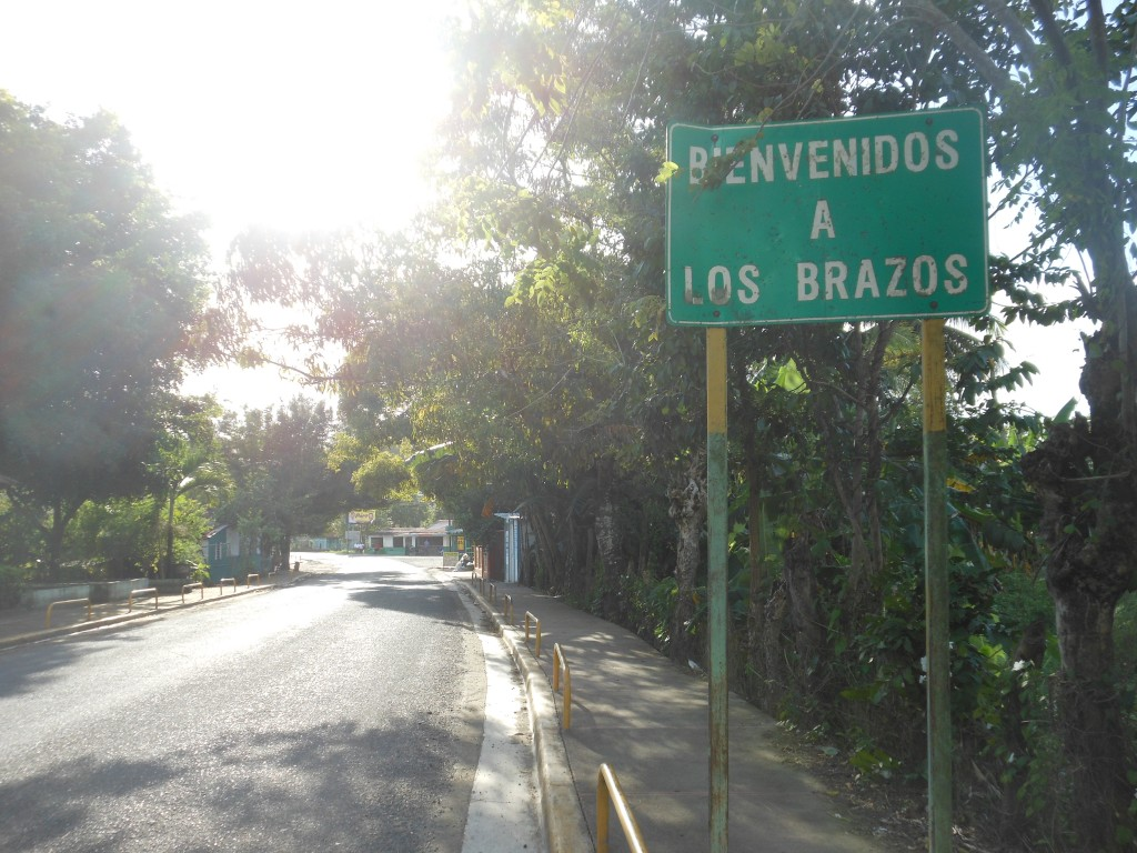 "The ""Bienvenidos a Los Brazos"" sign directly after the bridge, with the Los Brazos intersection visible in the distance."