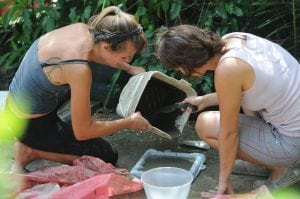 Selin and Peyton pouring a cement mixture into the frames to set.