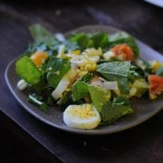 A picture perfect plate of farm fresh greens, eggs, tomatoes and avocado.